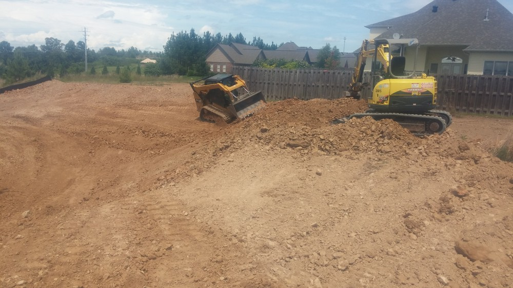 our skidsteer is grading the yard while the new house is being framed